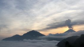 Sunrise above Lake Batur Covered with Clouds and Mount Agung Erupting Smoke - Seen from Top of Mount Batur in Bali, Indonesia. stock video