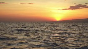 Sunrise above ocean viewed from boat. Sunrise above ocean and mountains viewed from boat stock footage