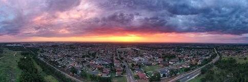 Sunrise above a residential suburbs with streets, homes parks in the background. Dramatic lighting and warm colours stock photos