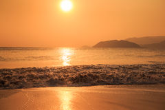 sunrise above sea against hills with running waves Stock Images