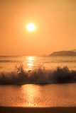 sunrise above sea against hills with running waves Royalty Free Stock Photo