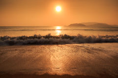 Sunrise above sea against hills with running waves Stock Photography