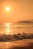 sunrise above sea against hills with running waves Stock Photo