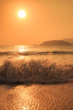 Sunrise above sea against hills with running waves Royalty Free Stock Photography