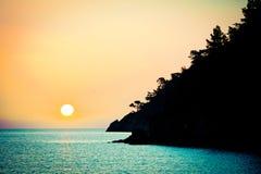 Sunrise above the sea silhouette of coast Stock Image