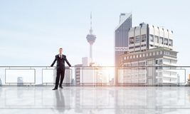 Sunrise above skyscrapers and businessman facing new day stock image