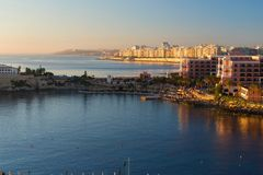 Sunrise above St. Julian ´s bay, Dragonara, Paceville and Sliema city, Malta. Panorama of sunrise above St. Julian ´s bay with buildings in Dragonara Royalty Free Stock Photography