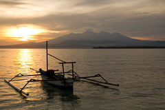 Sunrise above volcano Rinjani with fishing boat, L. Sunrise above volcano Rinjani with fishing boat in ocean, Lombok, Gili Islands stock images