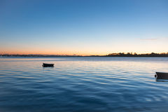 Sunrise across bay with small dinghy blue tones with orange arou Royalty Free Stock Photos