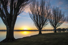 Sunrise across a lake. Bright sunrise viewed through trees as the sun crests the horizon Royalty Free Stock Image