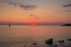 Sunrise in the adriatic sea with little boat Stock Photo