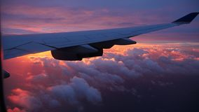 Sunrise from an airplane window above the clouds. The sun rises above the clouds seen from an airplane window royalty free stock photography