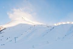 Sunrise at an alpine ski piste in winter. Blue sky and sunrise at a mountain in an alpine ski resort Stock Images