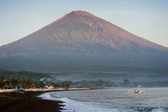 Sunrise in Amed, Bali, Indonesia. The active volcano Gunung Agung looms over the black sand beach of Jemeluk in the area known as Amed in the eastern shore of Royalty Free Stock Photography