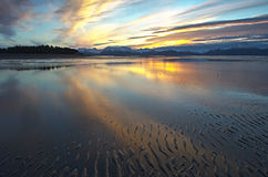 Sunrise Arc. Yellow rays of dawn reflect off a thin layer of water and wet sand on a beach near Homer Alaska Royalty Free Stock Photo