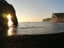 Sunrise through archway on beach Royalty Free Stock Images