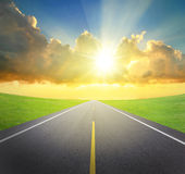 Sunrise with asphalt road and green grass Stock Images