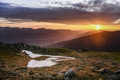 Sunrise in the Austrian Alps. The sun is rising over the summit of Hundskopf mountain, Tyrol, Austria, July 2018 stock image