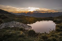 Sunrise in the Austrian Alps. The sun is rising over the summit of Hundskopf mountain, Tyrol, Austria, July 2018 royalty free stock images