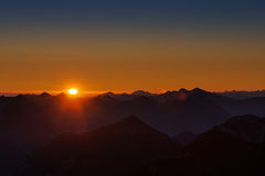 Sunrise in austrian mountains with glowing sun Royalty Free Stock Photo