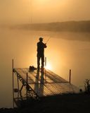Sunrise Bass Fishing. Fisherman casting from a dock in northern Iowa light fog and a golden sky. Moments that dont last long royalty free stock photo