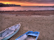 Sunrise on the beach. A colourful sunrise on the beach with boats on the foreground Royalty Free Stock Photography