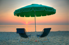 Sunrise on the Beach. Chairs and umbrella on a beach at sunrise Stock Photos