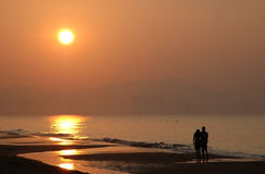 Sunrise beach. A couple were walking side by side along the hainan beach in china early in the morning Stock Images