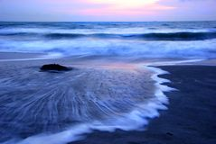 Sunrise Beach. A wave surges up the beach at dawn Stock Photography