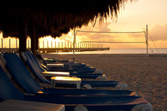 Sunrise on the Beach. Empty chairs early in the morning during sunrise. In the distance, the pier in Playa Del Carmen is silhouetted against the sky stock photo