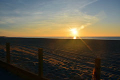 Sunrise at the Beach from Behind the Dunes Stock Photos