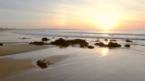 Sunrise on the beach with beige sand shore. Sunrise sea horizon summer beach. Sunset on beach. Tranquil idyllic scene of a golden sunset over the sea, waves stock footage