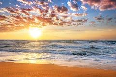 Sunrise the beach  with deep blue sky and sun rays. Stock Photos