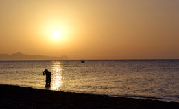 Sunrise beach. Diver on the sunrise background in Santorini Stock Photo
