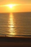 Sunrise on the Beach. Family walking the shoreline during the sunrise on the beach stock photo