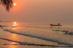 Sunrise Beach. And fisherman, fishing boat Stock Image