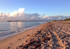 Sunrise at the beach. Sunrise glow at the beach with pier in the background Stock Image