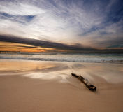 Sunrise on beach with log in foreground Stock Photo