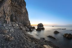 Sunrise on beach with rocks and sea Royalty Free Stock Photos