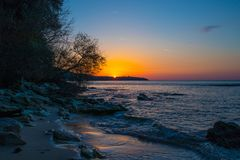 Sunrise on the beach with rocks and trees Royalty Free Stock Image
