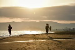 Sunrise on the beach with sea and running people royalty free stock photos