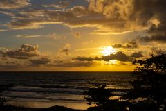 The sun hidden among dense clouds filters its rays on the sea. royalty free stock images