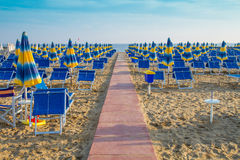 Sunrise beach with sun loungers and umbrellas. The Sunrise beach with sun loungers and umbrellas Stock Images