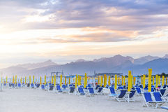 Sunrise beach view. Ready to open beach. Morning seats and umbrellas at seaside Stock Photos
