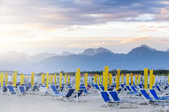 Sunrise beach view. Ready to open beach. Morning seats and umbrellas at seaside Stock Images