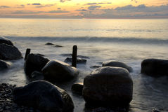 Sunrise at the beach water and stones Royalty Free Stock Photography