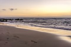 Sunrise on a beach with waves and stones Royalty Free Stock Photography