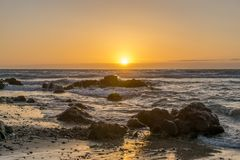 Sunrise on a beach with waves and stones Royalty Free Stock Image