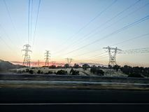 Sunrise with the beautiful hills and powerlines stock image