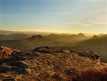 Sunrise in a beautiful mountain of Bohemian-Saxony Switzerland. Sandstone peaks and hills increased from foggy background Royalty Free Stock Photos